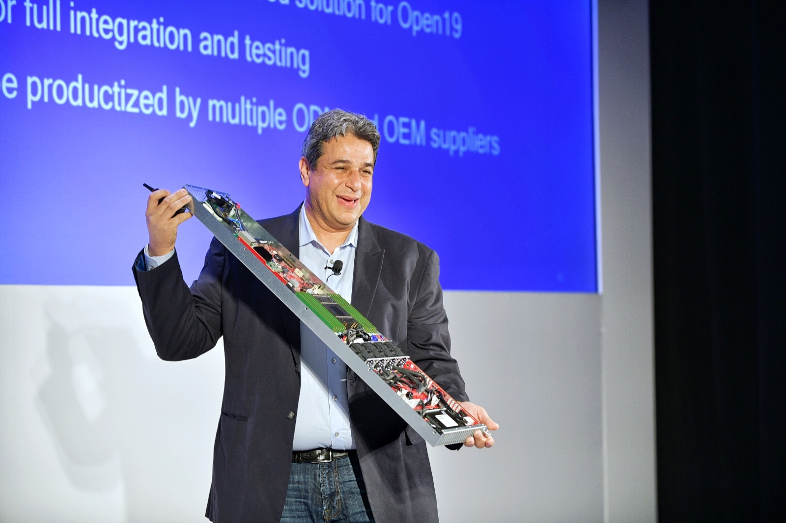Yuval Bacher holding server on stage at Qualcomm launch event